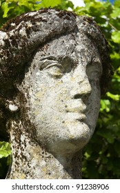 Weathered limestone figure head of garden statue.