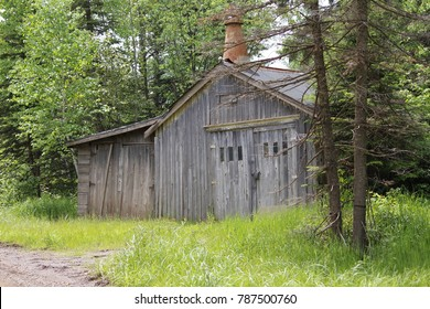 A weathered old garage in the middle of the woods.