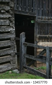 Weathered old log barn with a crooked gate.