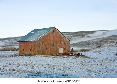 Weathered red barn on snow covered rolling hills of the Palouse region in Washington state