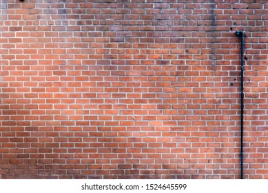 Weathered Red Brick Wall with Pipe