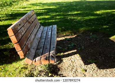 A weathered red park bench on a clear sunny day in shadow