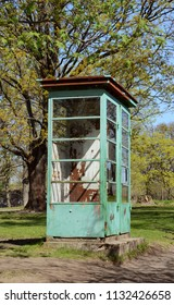 Weathered and rusted disused phone booth with peeling pale green paint on Suomenlinna island, Finland