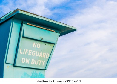 """weathered sign saying """"No Lifeguard On Duty"""" at lifeguard stand on the beach in Santa Barbara, California, USA with copy space"""