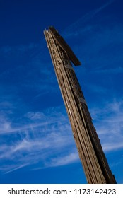 A weathered and splintered wood pole is pictured against a blue sky.