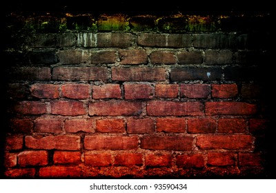 Weathered stained old brick wall with cracked and missing plaster