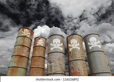Weathered steel toxic storage silo with skull and crossbones symbol rising up against a dramatic apocalyptic sky for the concept of environmental destruction.