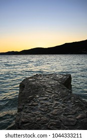 Weathered stone pier in blue sea at sunset
