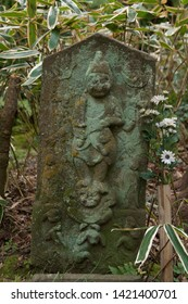 A weathered stone statue stands in the compound of Zuisen-ji temple in Kamakura, south of Tokyo, Japan.  The armed guardian deity stamps on an ogre.