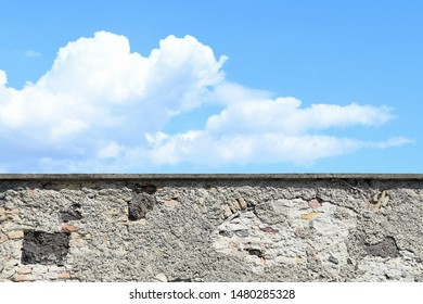 weathered stone wall with blue sky and cloud