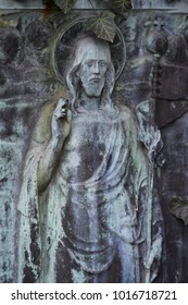 Weathered tombstone sculpture of Jesus Christ with ivy