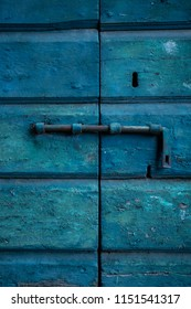 Weathered traditional wooden door with detail of rusty iron bolt.
