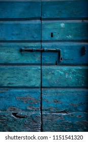 Weathered traditional wooden door locked with rusted iron bolt.