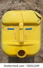 Weathered used yellow plastic tube on sand background imitating funny human face