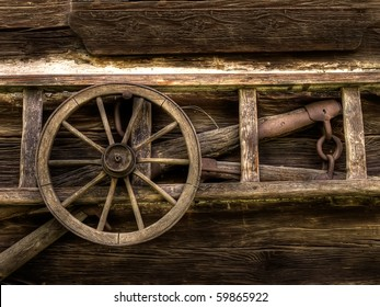 weathered wall of old barn with wooden ladder and wood coach wheel