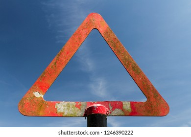Weathered warning sign against blue sky