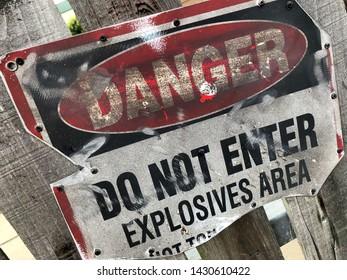 Weathered warning sign. Danger, do not enter. Explosives Area.