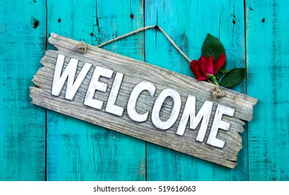 Weathered welcome sign with red flower hanging on antique rustic teal blue wood door; holiday background with home concept