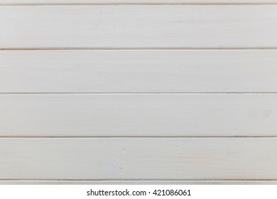 Weathered white wood background with knots and nail holes.