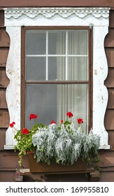 Weathered white-framed chalet window accented by red flowers