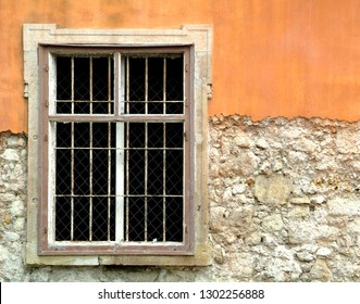 Weathered window frame on a partially orange stuccoed facade in Eger, Hungary