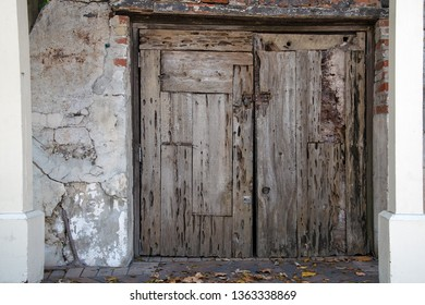 weathered wood closed house doors with grungy wall