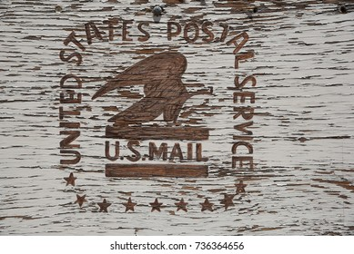 Weathered wood sign with U.S. Mail logo stenciled on it in Jerome, Arizona, July 7, 2017