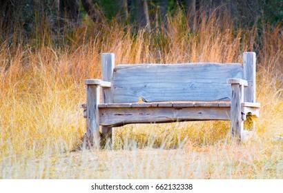 weathered wooden bench in field of prairie grass