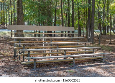 Weathered wooden bleachers in a grove of green trees