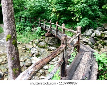 A weathered wooden bridge spans Gap Creek in Cumberland Gap National Park on a rainy summer day.