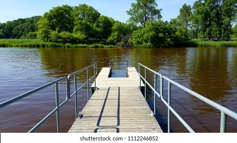 Weathered wooden dock with faded blue metal railings for kayaks & canoes on a river in the upper Midwest with trees & vegetation in the distance. Captured on a sunny afternoon. Spring/ Summer, 2017