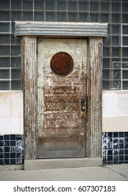 Weathered wooden door with a closed up round window in a wall with glass bricks