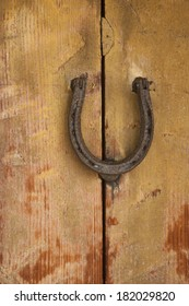 weathered wooden door with a rusty vintage horseshoe.
