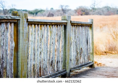 weathered wooden fence in field of prairie grass