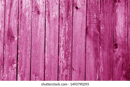 Weathered wooden fence in pink color. Abstract background and texture for design.