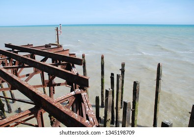 Weathered wooden posts and iron sub structure of the Victorian pier at Hastings in East Sussex, England.