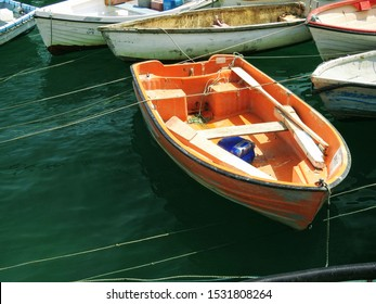 Weathered wooden rowing boat tied down in Mevagissey harbor. Cornwall, UK