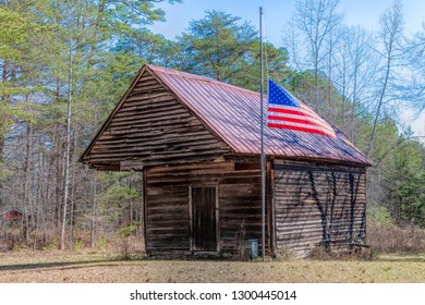 Weathered wooden shed or cabin in Dahlonega. There is a half-mast American flag waving in the wind. Beauty of rural areas in the Georgia state