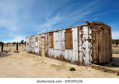 A weathered, wooden shed standing in the middle of abandoned land.