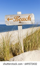 Weathered wooden sign showing direction to the beach