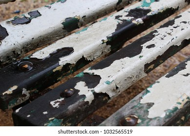 Weathered wooden slats with peeling white paint, wet with rain