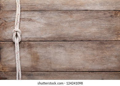 Weathered wooden table background with rope reef knot, top view