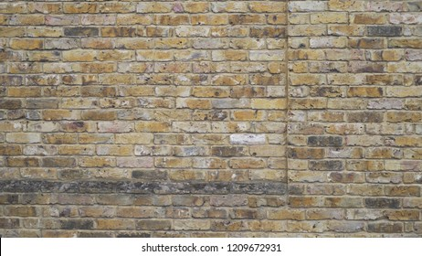 Weathered yellow and grey brick wall in Windsor, England. Aged multicolored wall background texture for compositing. 4k