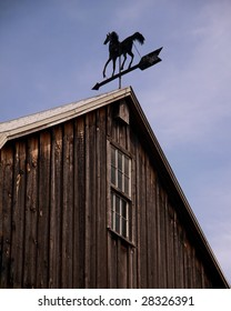 A weathervane atop a barn indicates the direction of the wind.