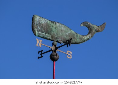 Weathervane in the shape of a whale against clear blue sky