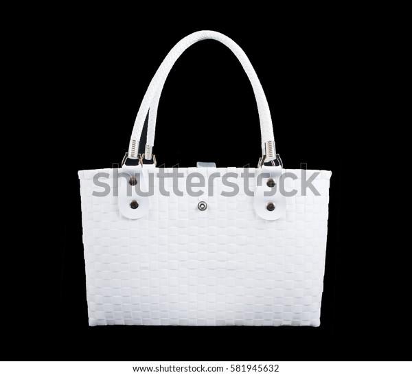 Weave white handbag isolated on black background. White hand bag isolated