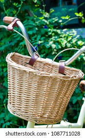 Weaved basket in front of foldable bicycle with plant background