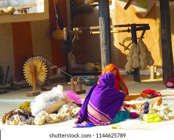 Weaver ladies in an Indian village with spinning wheel in the background at Kutch, India