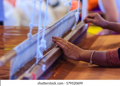 Weaver using small loom or weaving machine for weaving fabric. Weaver is weaving show and teaching to the tourist at the night market.