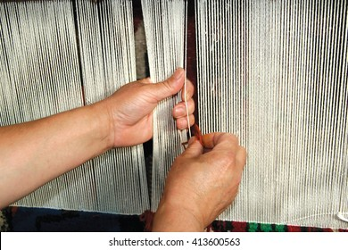 Weaving carpet with traditional techniques on a loom. Wool yarns used as a  warp and weft is crucial for this art.